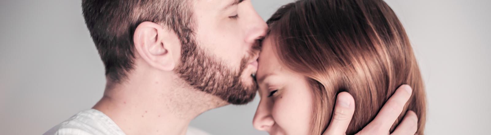 Ein Mann küsst eine Frau auf den Kopf