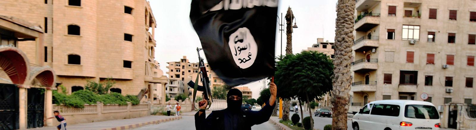 Ein bewaffneter und vermumter Mann schwenkt in Rakka die IS-Flagge