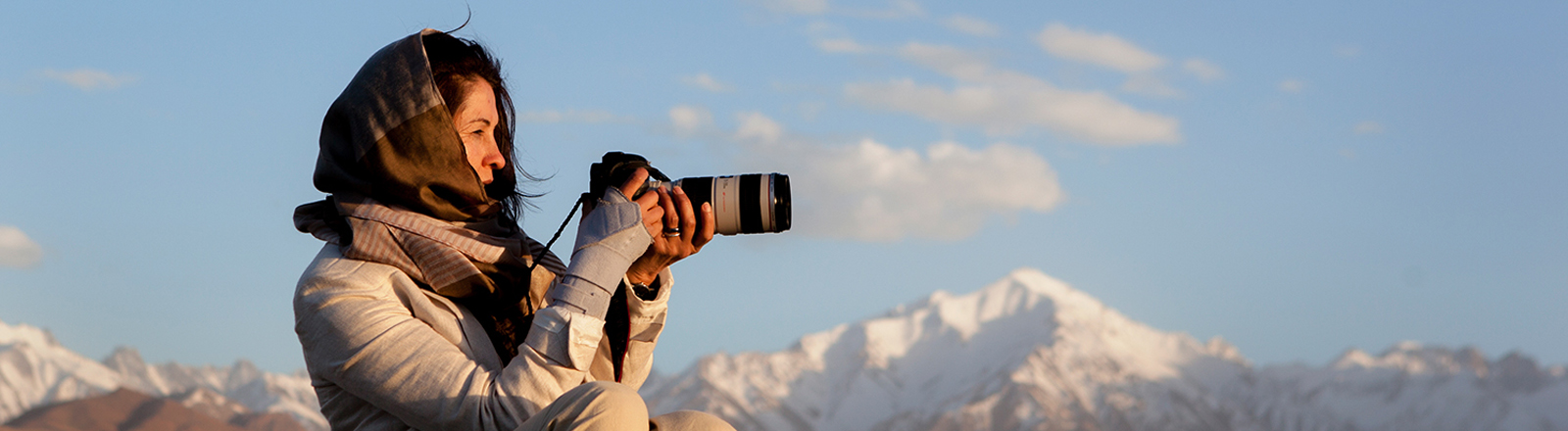 Lela Ahmadzai mit ihrer Kamera vor einem Bergpanorama