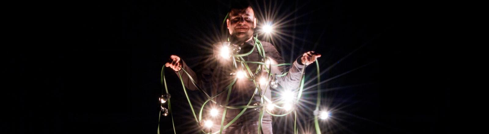 Eine Mann hält eine Lichterkette