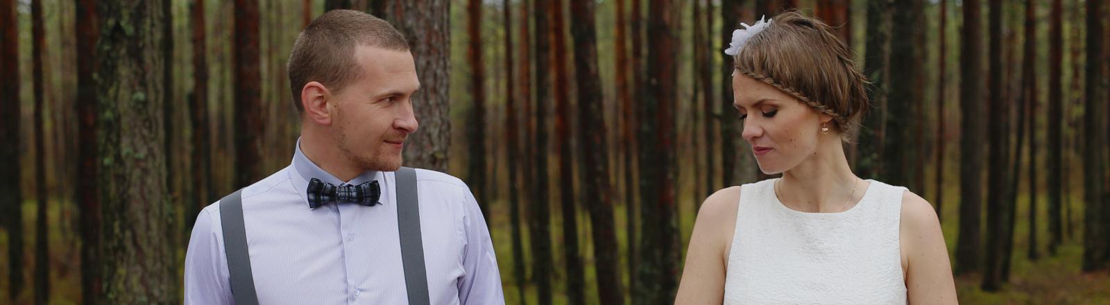 Ein Paar schaut sich im Wald in die Augen