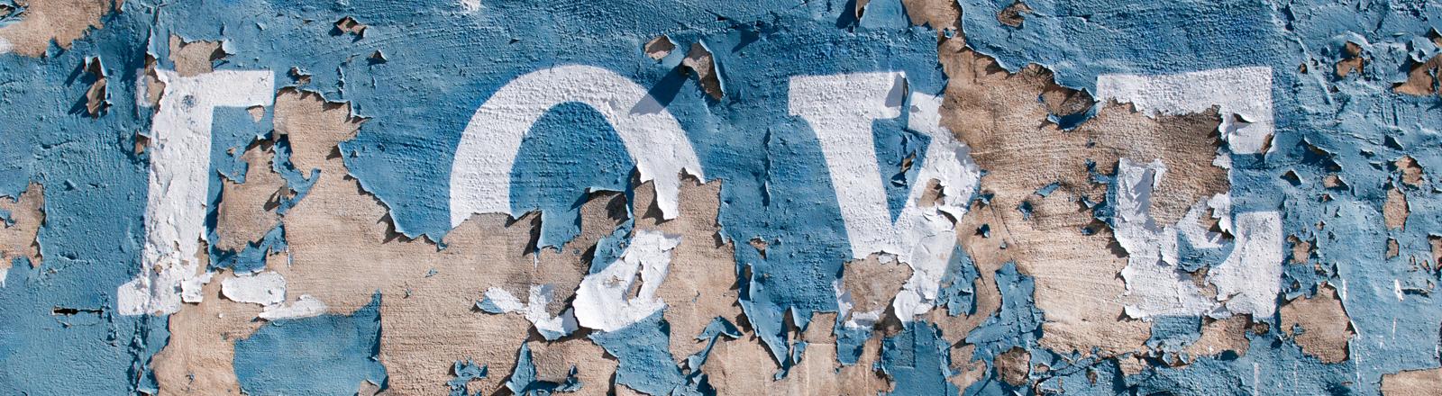 Das Wort Love ist an eine verwitterte Wand geschrieben