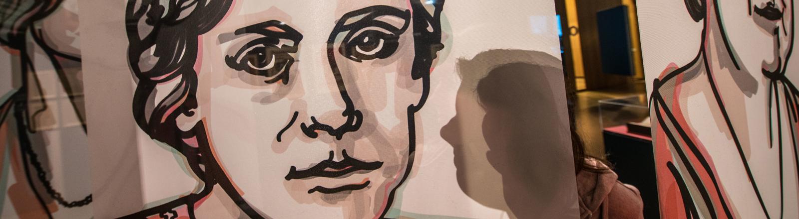 Hessen, Frankfurt/Main: Eine Besucherin der Ausstellung «Damenwahl» steht im Historischen Museum Frankfurt hinter einer Fahne, auf der Marie Juchacz, Gründerin der Arbeiterwohlfahrt (AWO), abgebildet ist. Seit 100 Jahren können Frauen in Deutschland wählen gehen und gewählt werden. Jetzt wird dieses Kapitel der Geschichte neu entdeckt. (zu dpa ««Wir gehören in dieses Haus» - 100 Jahre Frauenwahlrecht» vom 01.11.2018)