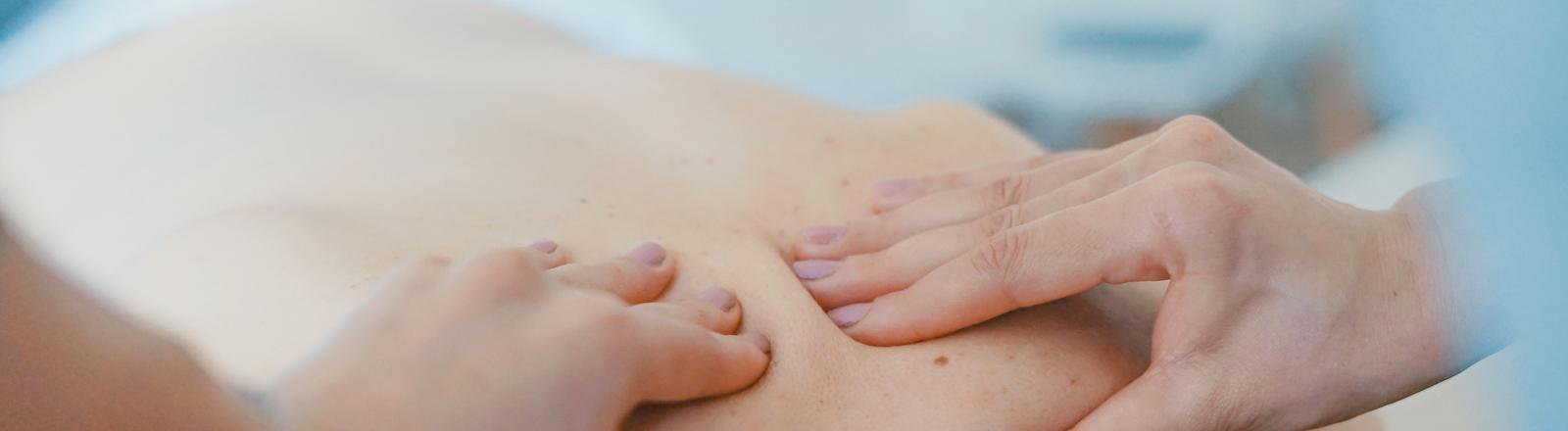 Zwei Hände massieren einen Rücken