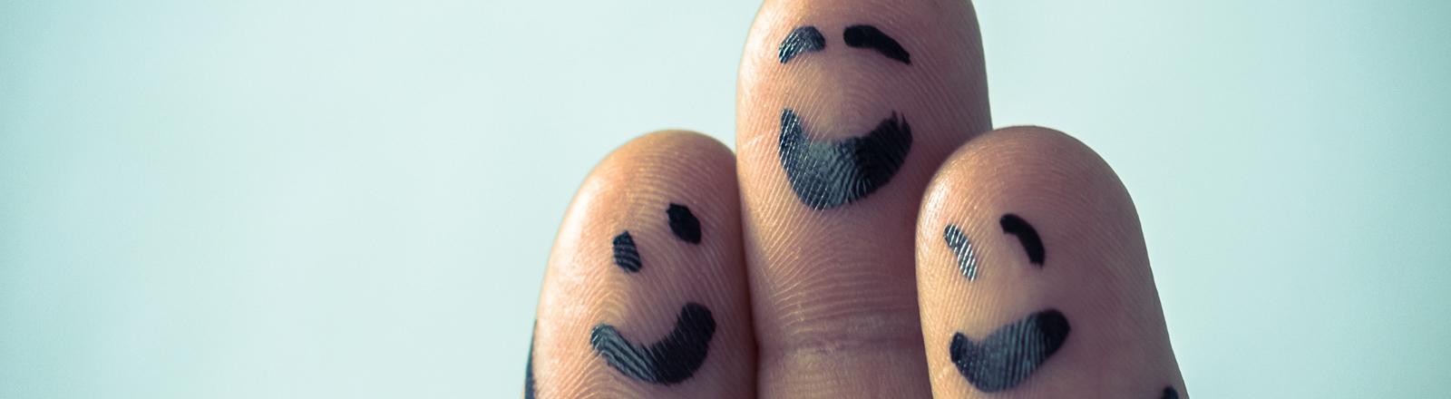 Drei Finger einer Hand. Auf jeden Finger ist ein lachendes Gesicht gemalt.