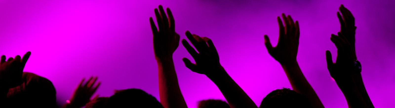 Menschen recken die Arme bei einem Konzert in die Höhe
