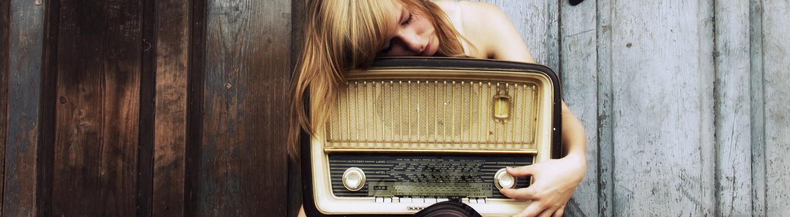 Ein Frau mit einem alten Radio