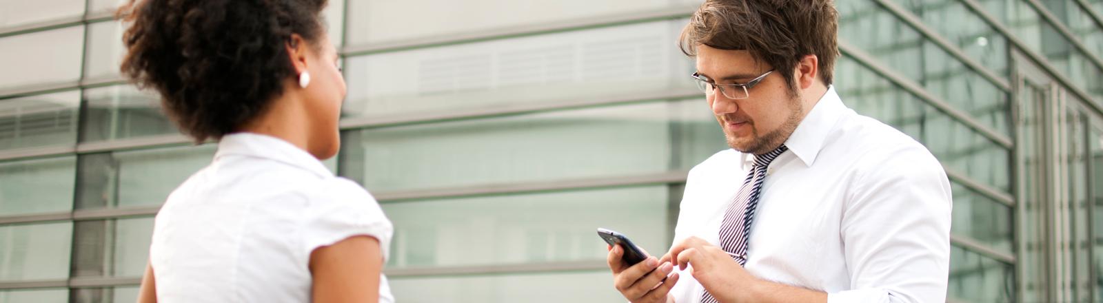 Ein Mann tippt auf seinem Smartphone - eine Frau schaut zu