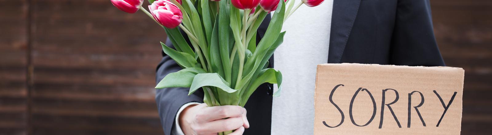 """Ein Mann mit einem Blumenstrauß und einem Schild mir der Aufschrift """"Sorry"""""""