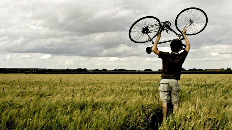 Ein Mann steht in einem Feld und hält ein Fahrrad über den Kopf.