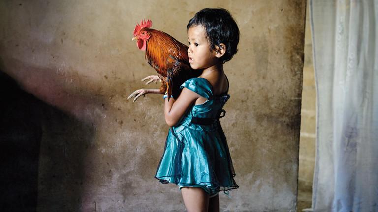 Mädchen mit einem Hahn auf dem Arm