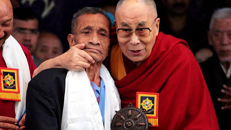 """Der Dalai Lama beglückwünscht Naren Chandra Das, einen ehemaligen indischen Soldaten der Teil einer Gruppe war, die den Dalai Lama im Jahr 1959, während der """"Thank-You-India""""- Veranstaltung, die von der tibetanischen Exilregierung am 31.03.2018 im indischen Dharamsala organisiert wurde."""