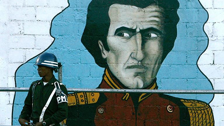 Ein venezolanischer Soldat steht in der Stadt venezolanischen Hauptstadt Caracas vor einem Wandgemälde von Simon Bolivar.