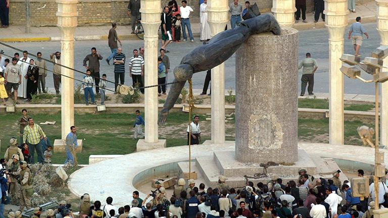 Iraker stehen auf einem Platz in Bagdad und schauen zu, wie die Statue von Diktator Saddam Hussein zu Fall gebracht wird (09.04.2003); Foto: dpa