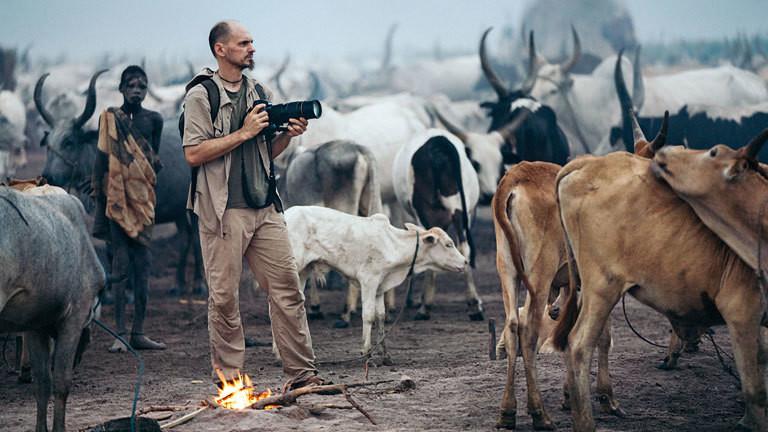 Fotograf Markus Mauthe im Südsudan neben Rindern