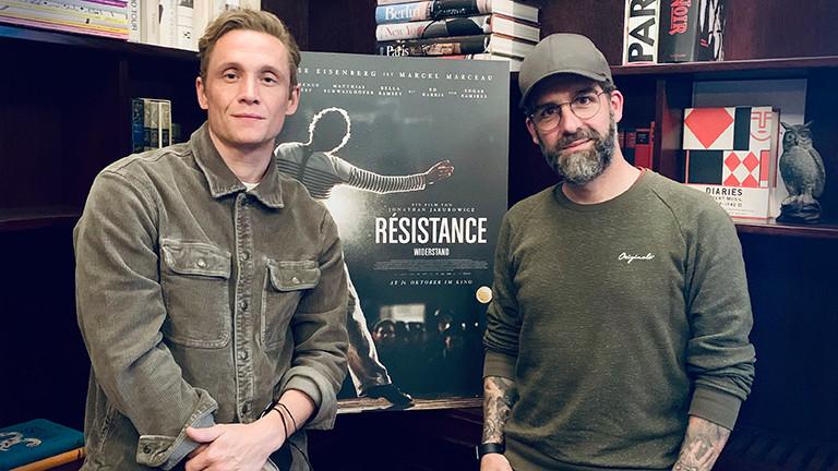 """Matthias Schweighöfer mit Tom Westerholt vor dem Filmplakat von """"Résistance"""""""