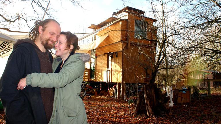 Nicole und Cartsen Dau umarmen sich, im Hintergrund ihr 25 Quadratmeter großes Haus.