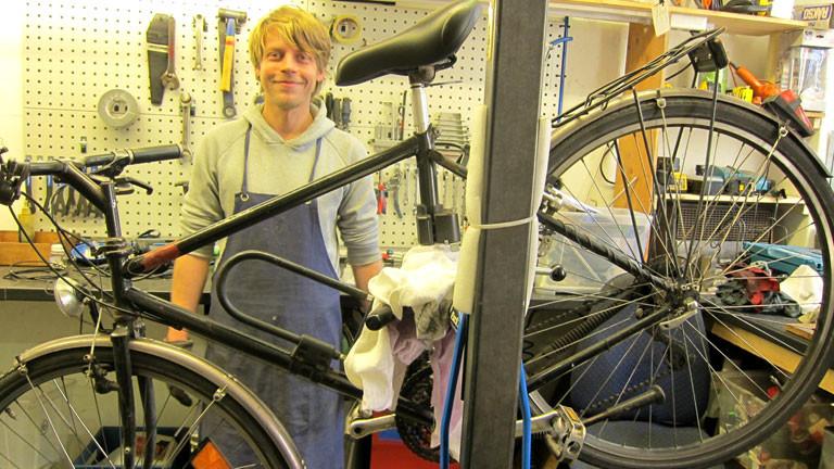 Ein Mann mit blauer Schürze vor einem Fahrrad.