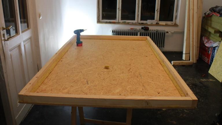 Für die Bodenplatte wird erst ein Lattenrahmen angeschraubt.