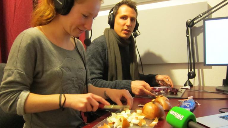 Ein Mann und eine Frau kauen Kaugummi und schneiden Zwiebeln