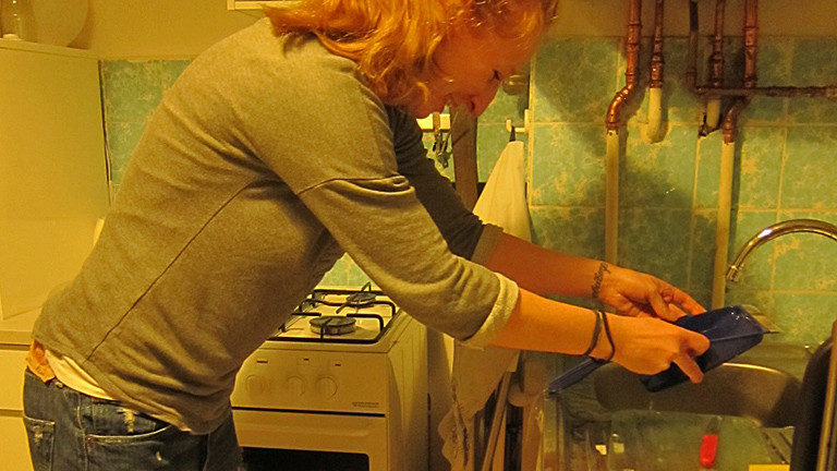 Eine Frau gießt Wasser über eine Kehrschaufel ab