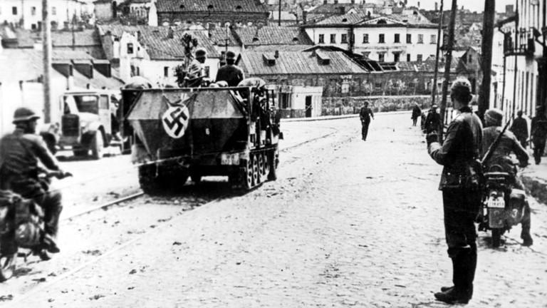 Ein Panzerfahrzeug der Wehrmacht, gefolgt von Soldaten auf Motorrädern, in der Stadt Minsk während des Russlandfeldzuges im August 1941.