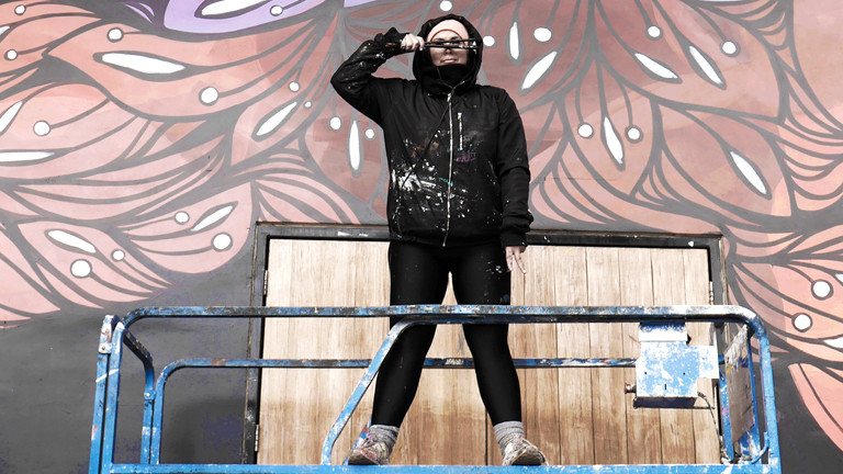 Frau mit Malerrolle auf einer Tribüne.