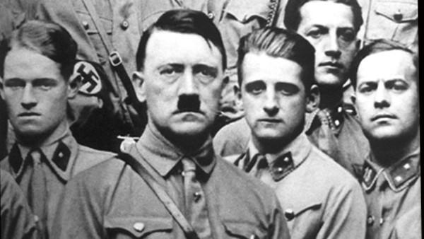 Hitler mit mehreren Anhängern im Hintergrund.