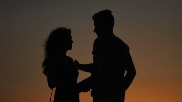 Ein verliebtes Paar am Strand bei Sonnenuntergang. Man kann sie nicht erkennen.
