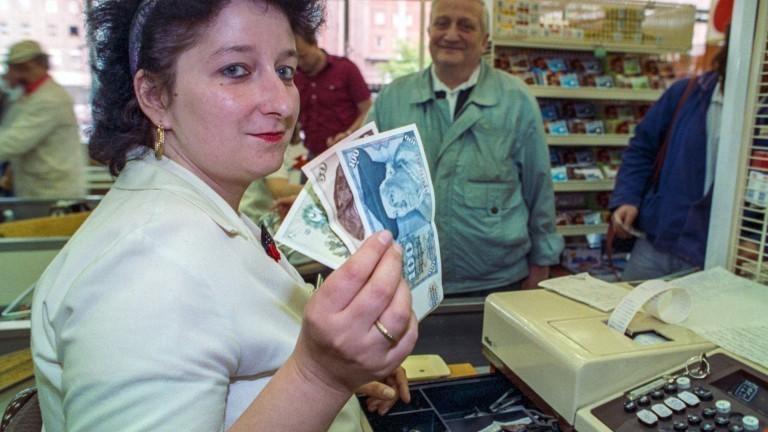 Eine Kassiererin mit D-Mark-Einnahmen in Ost-Berlin am ersten Tag nach Einführung der Deutschen Mark im Juli 1990.
