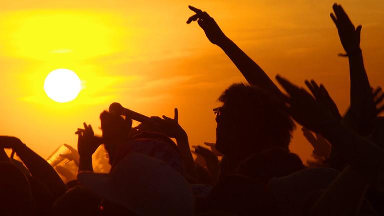 Auf einem Festival jubeln die Fans im Sonnenuntergang.