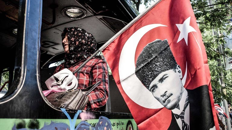 Eine türkische Frau mit Kopftuch und Anonymous-Maske, die eine Flagge mit dem Konterfei Atatürks in der Hand hält.