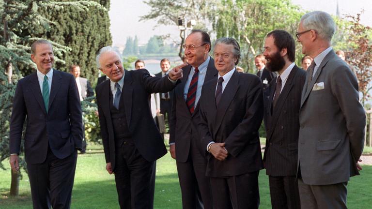 """Gruppenbild auf einer Wiese am Rhein (l-r): James Baker (USA), Eduard Schewardnadse (UdSSR), Hans-Dietrich Genscher (Bundesrepublik), Roland Dumas (Frankreich), Markus Meckel (DDR) und Douglas Hurd (Großbritannien). Am 5. Mai 1990 fand in Bonn die erste Runde der """"Zwei-plus-Vier""""-Konferenz statt."""