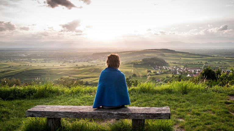 Frau sitzt auf einer Bank vor einem Panorama.
