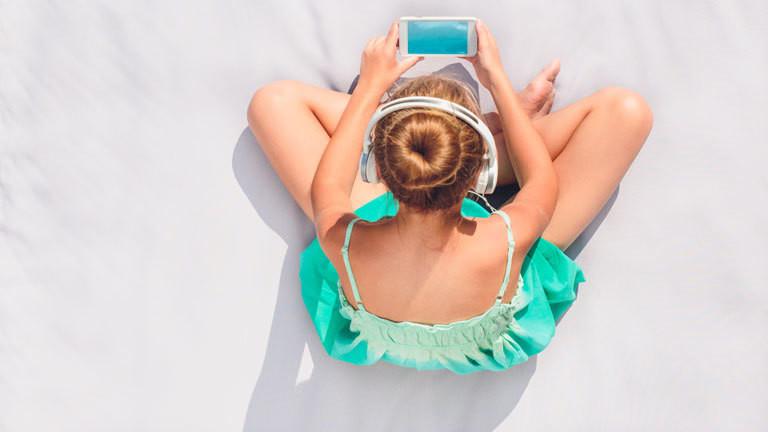 Eine Frau sitzt mit ihrem Smartphone in der Sonne.