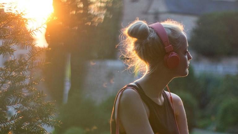 Frau hört mit Kopfhörer.