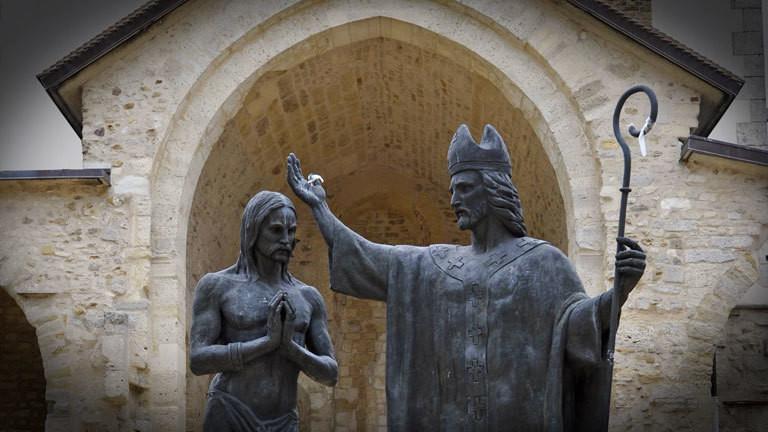 Standbild Heiliger St. Remigius tauft König Chlodwig vor der Abteikirche Saint-Remi in Reims.