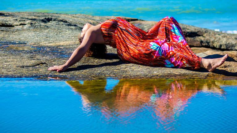 Frau räkelt sich am Strand.