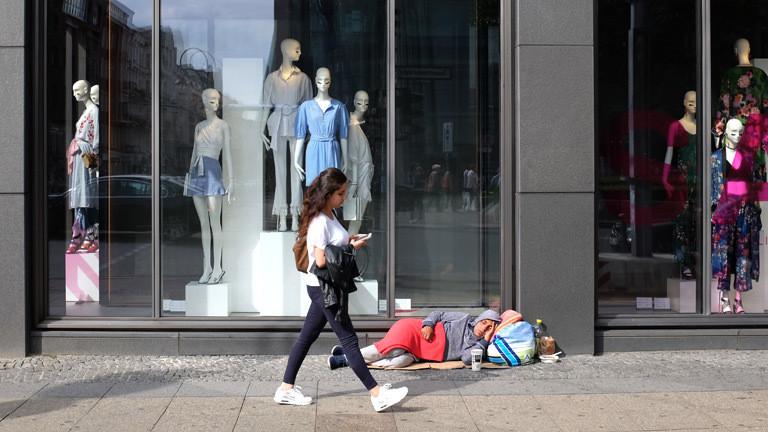 Passanten gehen achtlos an einem Obdachlosen vorüber, der auf der Tauentzienstraße auf dem Boden liegt.