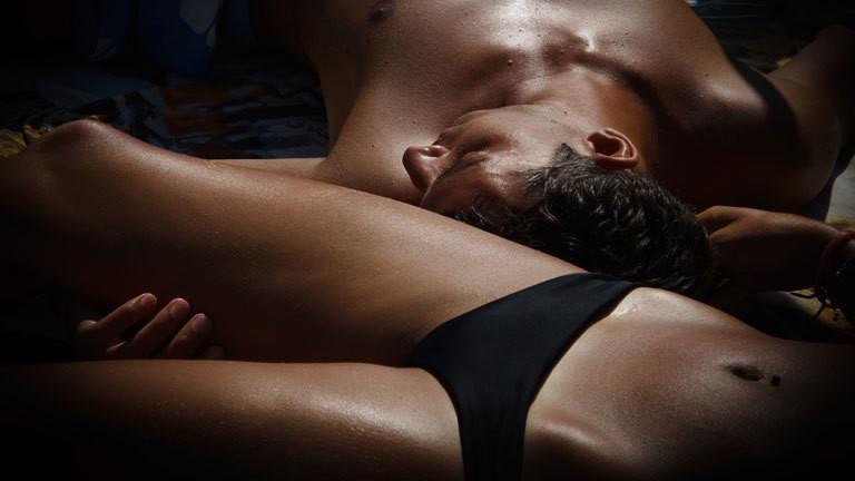 Frau und Mann liegen nackt nebeneinander.