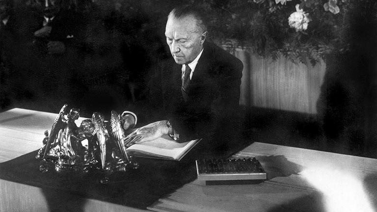 Der Präsident des Parlamentarischen Rates, Dr. Konrad Adenauer, bei der Unterzeichnung des Grundgesetzes am 23. Mai 1949 in Bonn.