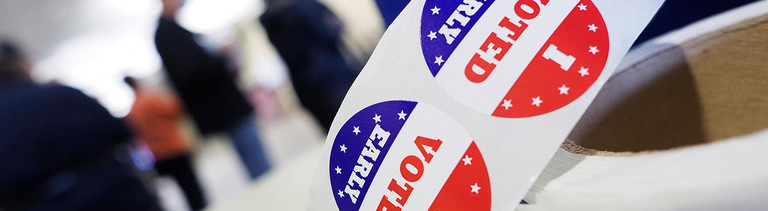 """Im Vordergrund liegt eine Rolle mit runden Aufklebern, auf denen steht """"I voted early""""; im Hintergrund sind verschwommen Menschen zu erkennen (4.10.2020)"""