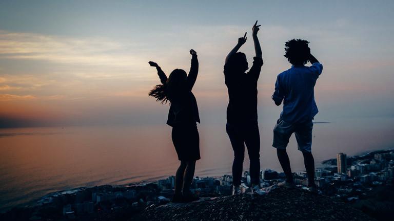 Drei Menschen im Sonnenuntergang an einem See