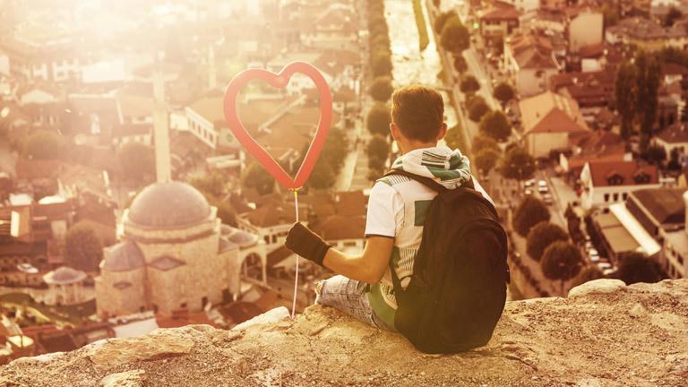 Ein Mann sitzt mit einem Herz in der Hand auf einem Fels und guckt sich eine Stadt von oben an
