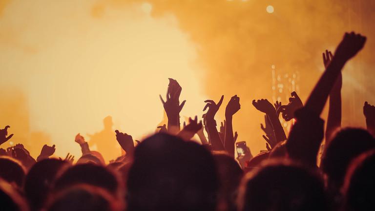 Publikum im Gegenlicht vor einer Konzertbühne
