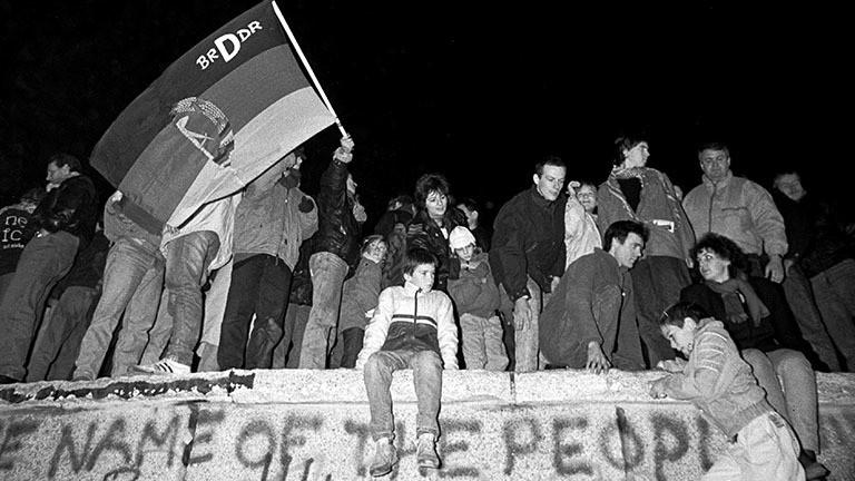 Menschen stehen und sitzen auf der Berliner Mauer in der Nacht vom 9. auf den 10 November 1989.