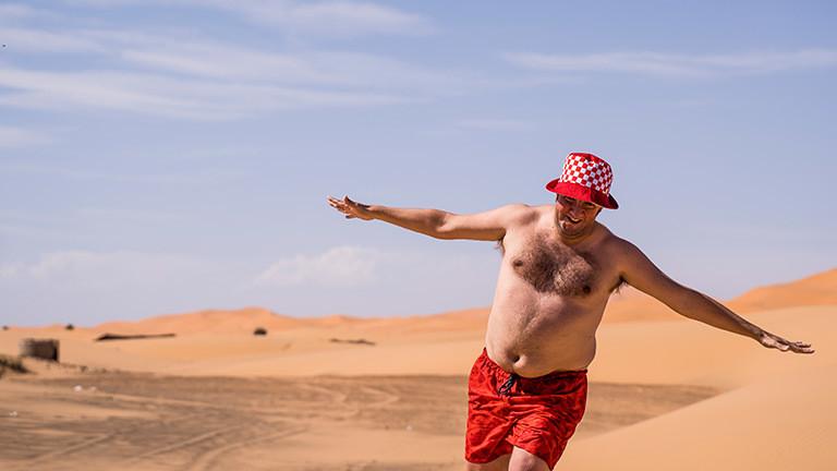 Mann mit nacktem Oberkörper in der Wüste