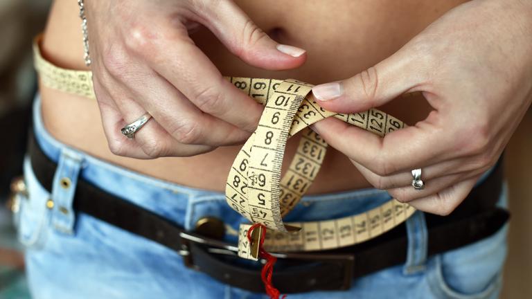 Eine Frau schlingt ein Maßband um ihren schlanken Bauch.