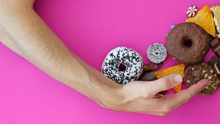 Eine Hand greift nach vielen Süßigkeiten.