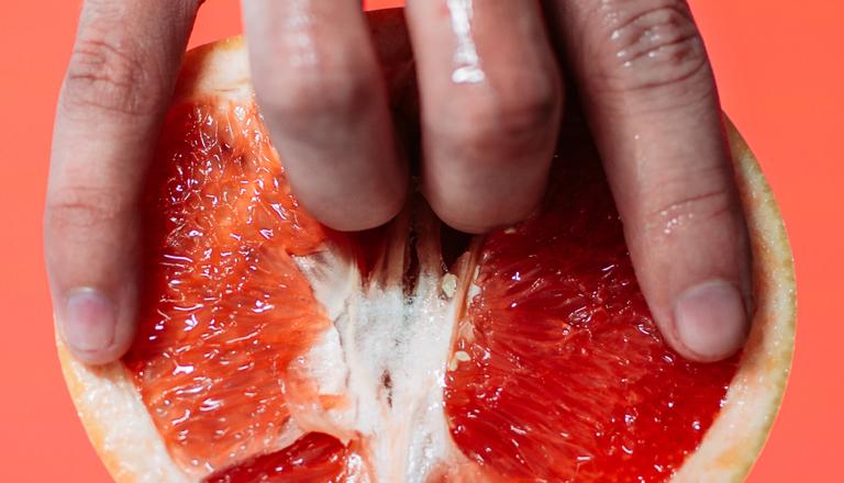 Symbolbild für weibliche Ejakulation: Eine feuchte Hand steckt zwei Finger in eine halbierte Grapefruit.